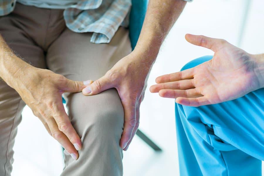גבר בטיפול תופס את הברך שלו